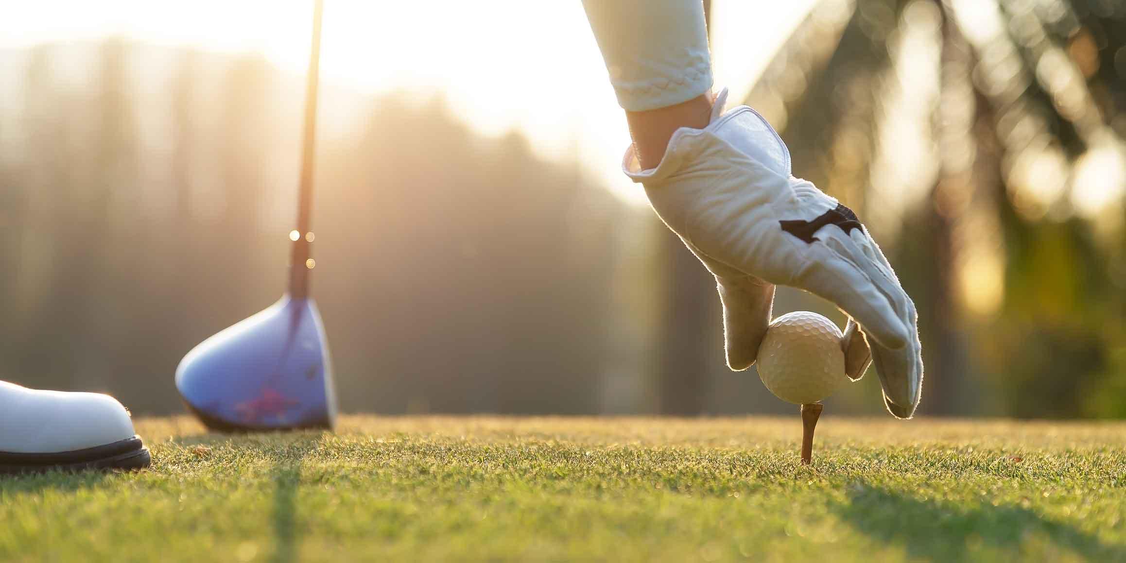 Golfer wearing white glove with golfing club in hand